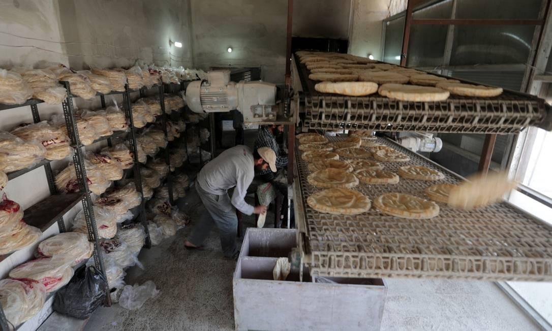 Trabalhadores preparam pilhas de pão dentro de uma padaria para o iftar no mês de jejum muçulmano do Ramadã, na cidade de Idlib Foto: KHALIL ASHAWI / REUTERS