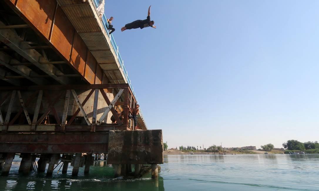 Um homem pula de uma ponte sobre o rio Eufrates em um dia quente em Raqqa, na Síria Foto: ABOUD HAMAM / REUTERS