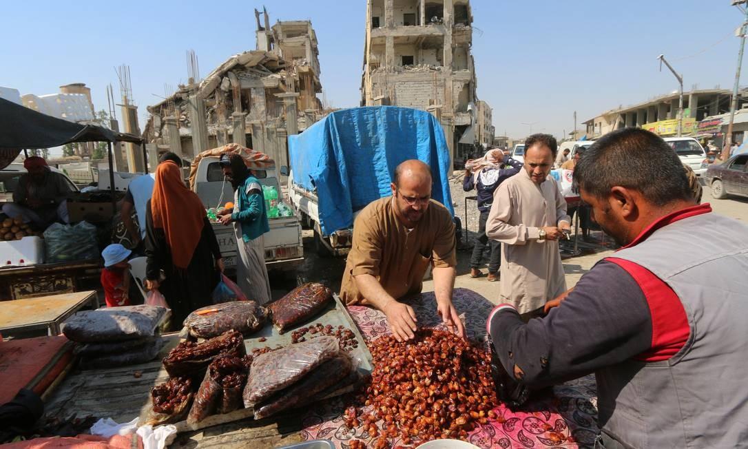 Um vendedor de rua atende seus clientes perto de edifícios danificados durante o mês sagrado do Ramadã, em Raqqa Foto: ABOUD HAMAM / REUTERS