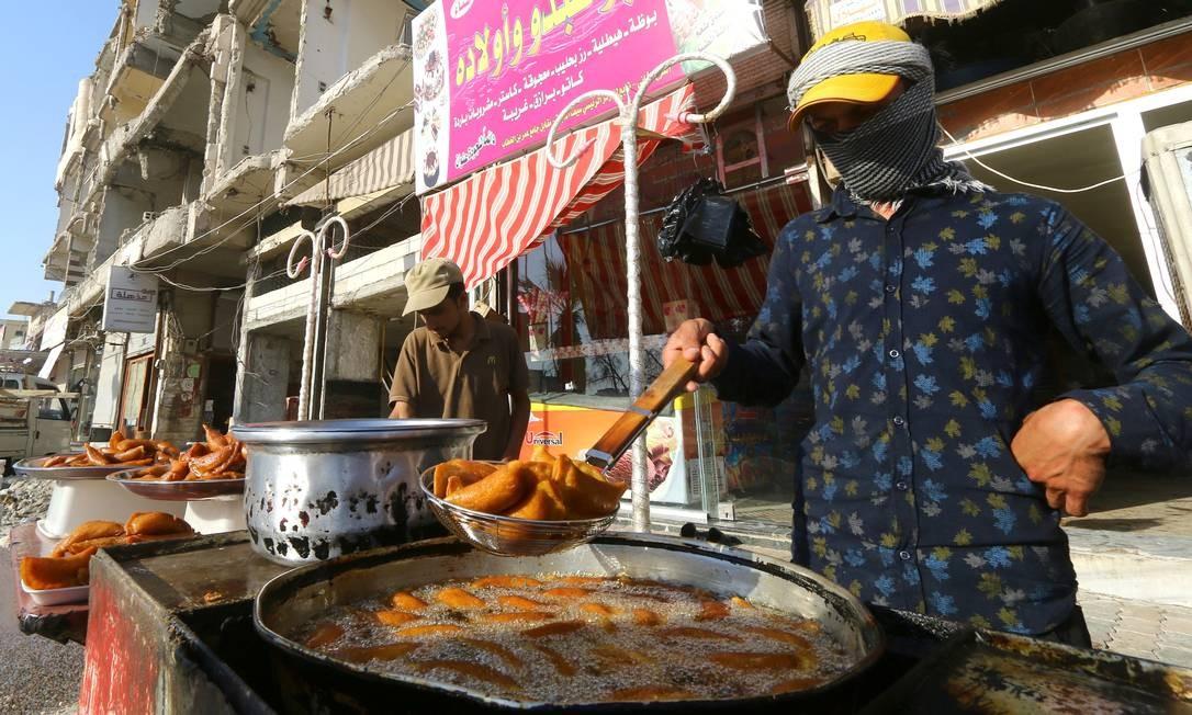 Um vendedor prepara doces tradicionais para venda em Raqqa Foto: ABOUD HAMAM / REUTERS