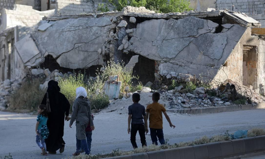 As pessoas andam perto de entulho de edifícios danificados na cidade de Idlib Foto: KHALIL ASHAWI / REUTERS