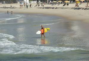 Surfistas praticam nas águas do Leme: últimas medições do Inea indicam que a praia está imprópria para banho Foto: Bruno Kaiuca / Agência O Globo