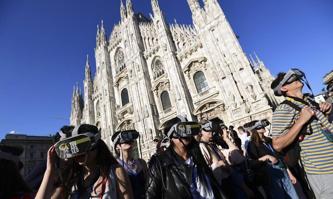 Turistas com os óculos de realidade virtual em frente à Catedral Duomo, em Milão, durante o tour You Are Leo Foto: MIGUEL MEDINA / AFP