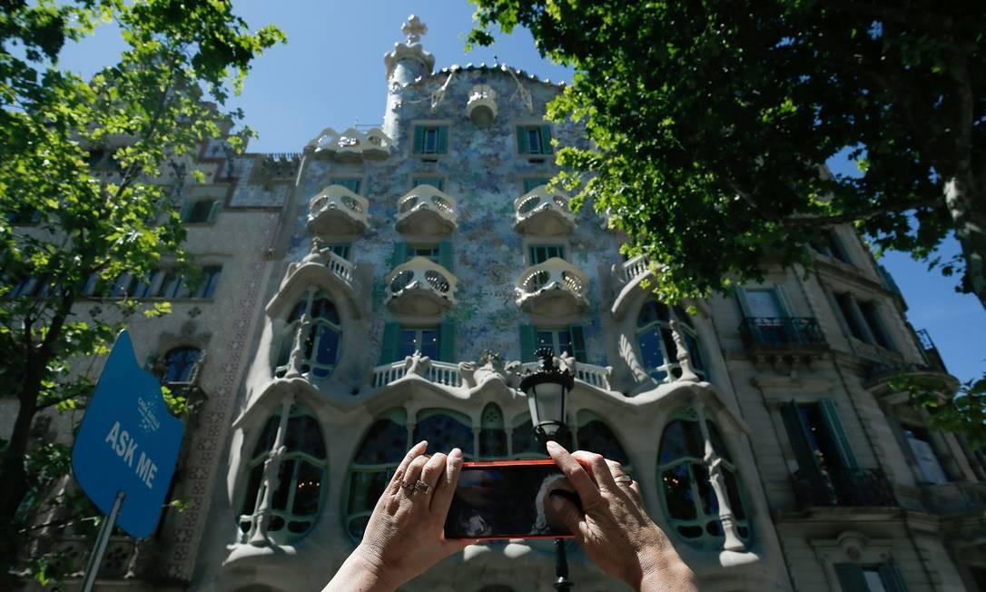 Turista fotografa a Casa Batlló, uma das construções mais conhecidas de Antoni Gaudí em Barcelona, que passou por três meses de restauração Foto: PAU BARRENA / AFP