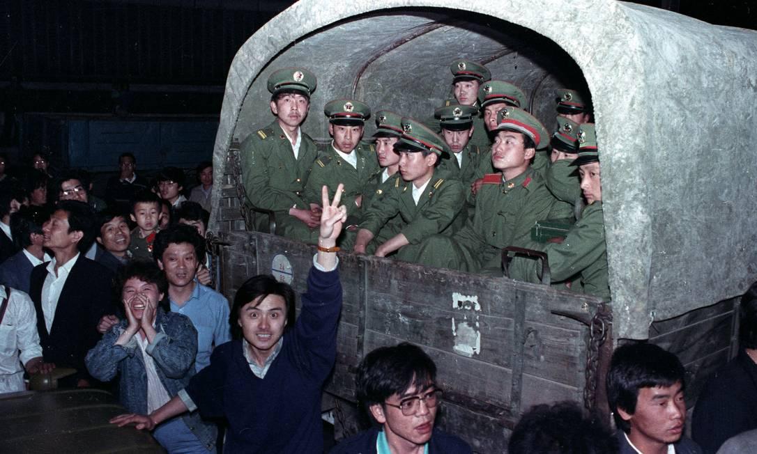 Moradores de Pequim cercam um comboio do Exército com 4 mil soldados em 20 de maio de 1989, em um subúrbio da cidade, para evitar que continue até a Praça da Paz Celestial, onde estavam os estudantes pró-democracia Foto: STRINGER / REUTERS