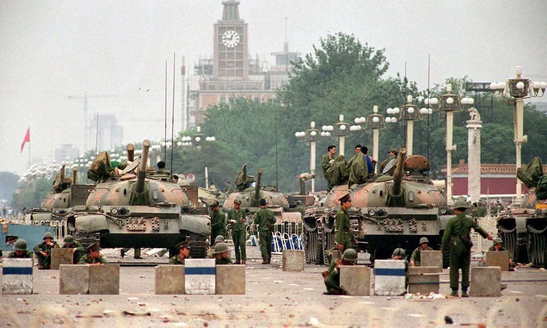 Tanques do Exército Popular de Libertação e soldados guardam a Avenida Chang'an, que leva à Praça da Paz Celestial, em Pequim, dois dias após a repressão aos manifestantes Foto: Greg Baker e Manny CENETA / AFP