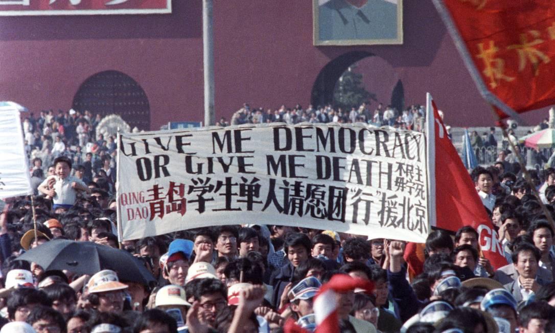 """Estudantes chineses carregam uma placa que diz """"Dê-me democracia ou me dê a morte"""" durante uma manifestação na Praça da Paz Celestial em Pequim, em 14 de maio de 1989 Foto: STRINGER / REUTERS"""