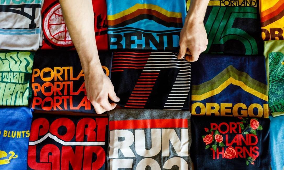 Camisetas coloridas e com estética vintage são os destaques da loja Grafletics, em Portland, no Oregon Foto: Leah Nash / The New York Times