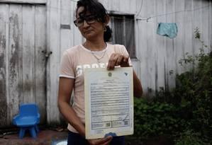 Revolta: Girlane, mãe de uma das vítimas do massacre, mostra certidão de óbito do filho: 'Morreu sem ser ouvido' Foto: Raphael Alves / Agência O Globo