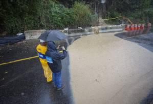 Funcionários da Prefeitura atuavam no local para facilitar escoamento, mas cachoeira de lama invadiu avenida durante o temporal Foto: Bruno Kaiuca / Agência O Globo