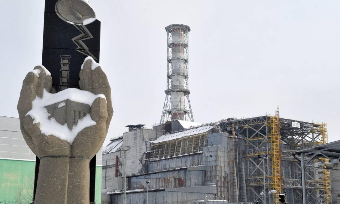 Memorial para as vítimas do desastre de Chernobyl diante do sarcófago da unidade do reator 4 em Chernobyl, em fevereiro de 2011 Foto: SERGEI SUPINSKY / AFP PHOTO