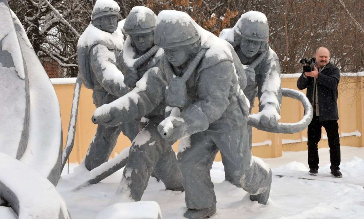 Um visitante fotografa o monumento em homenagem aos bombeiros de Chernobyl em fevereiro de 2011 Foto: SERGEI SUPINSKY / AFP PHOTO