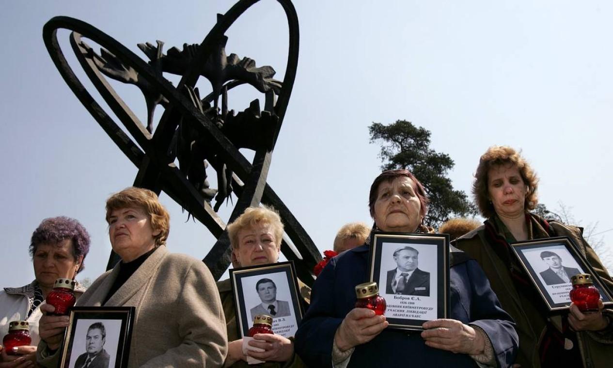 Viúvas de mortos em Chernobyl seguram fotos de seus maridos diante de um monumento em homenagem às vítimas da usina em Kiev, na Ucrânia, em abril de 2006 Foto: Denis Sinyakov / AFP PHOTO