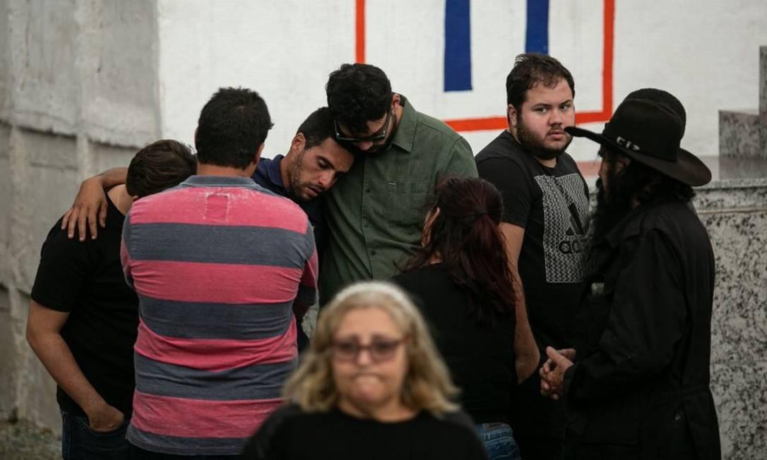 O namorado de Marcela é abraçado por amigos durante o enterro da jovem Foto: Brenno Carvalho / Agência O Globo
