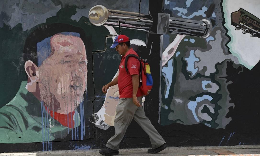Homem passa em frente à mural com homenagem ao ex-presidente da Venezuela Hugo Chávez em Sabaneta, no Estado de Barinas, na Venezuela Foto: YURI CORTEZ / AFP 31-5-19