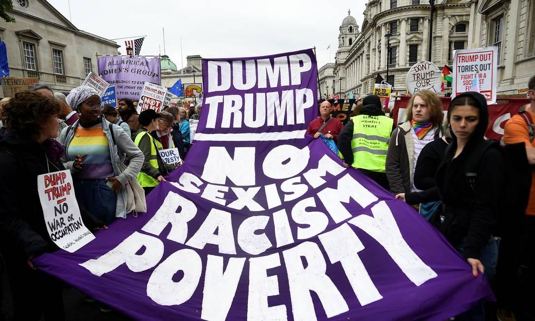 """Manifestantes carregam faixas que dizem """"descartem o Trump"""" e """"Não ao sexismo, ao racismo e à pobreza"""" Foto: CLODAGH KILCOYNE / REUTERS"""