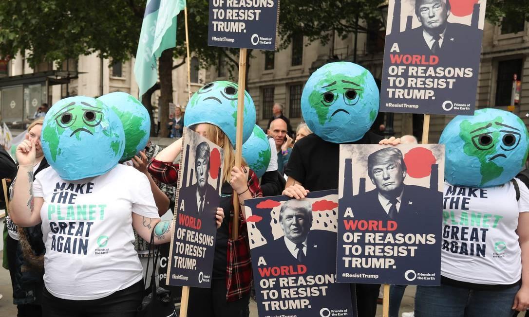 """Ativistas ambientais vestem máscara de planeta Terra chateado e carregam cartazes que diz """"Um mundo de razões para resistir a Trump"""" Foto: ISABEL INFANTES / AFP"""