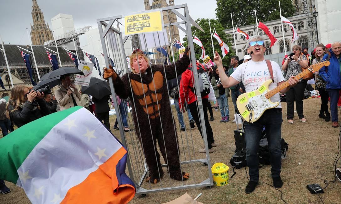Homem protesta dentro de jaula com máscara de Trump e roupa de macaco Foto: ALKIS KONSTANTINIDIS / REUTERS