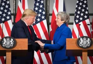 Trump e Theresa May se cumprimentam durante coletiva de imprensa em Londres Foto: STEFAN ROUSSEAU / AFP