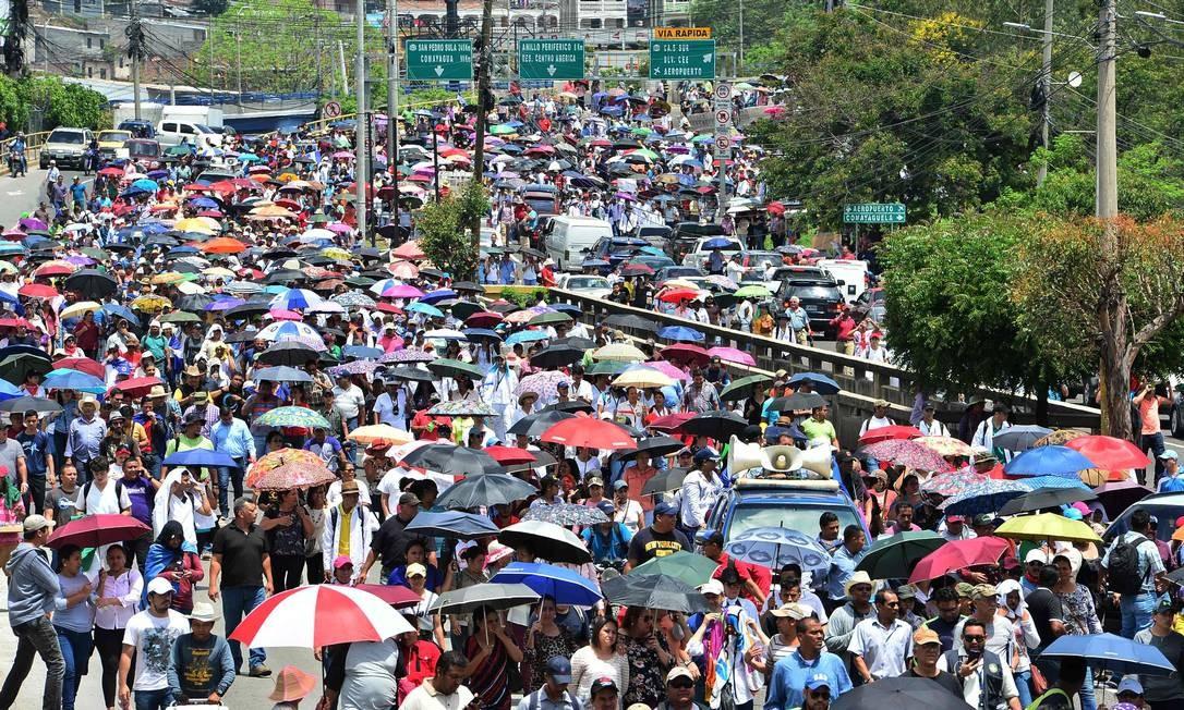 Manifestantes dos setores de educação e saúde marcham contra as reformas do governo em Tegucigalpa, capital hondurense Foto: ORLANDO SIERRA / AFP