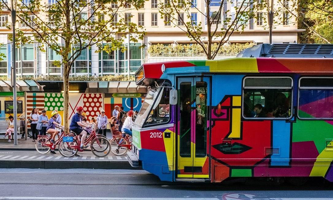 Turistas de bicicleta passam por um bonde colorido em Swanston Street, no centro de Melbourne, na Austrália Foto: Asanka Brendon Ratnayake / The New York Times