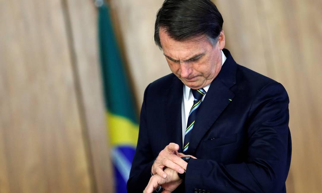 Bolsonaro confere o relógio durante cerimônia no Palácio do Planalto Foto: ADRIANO MACHADO / REUTERS