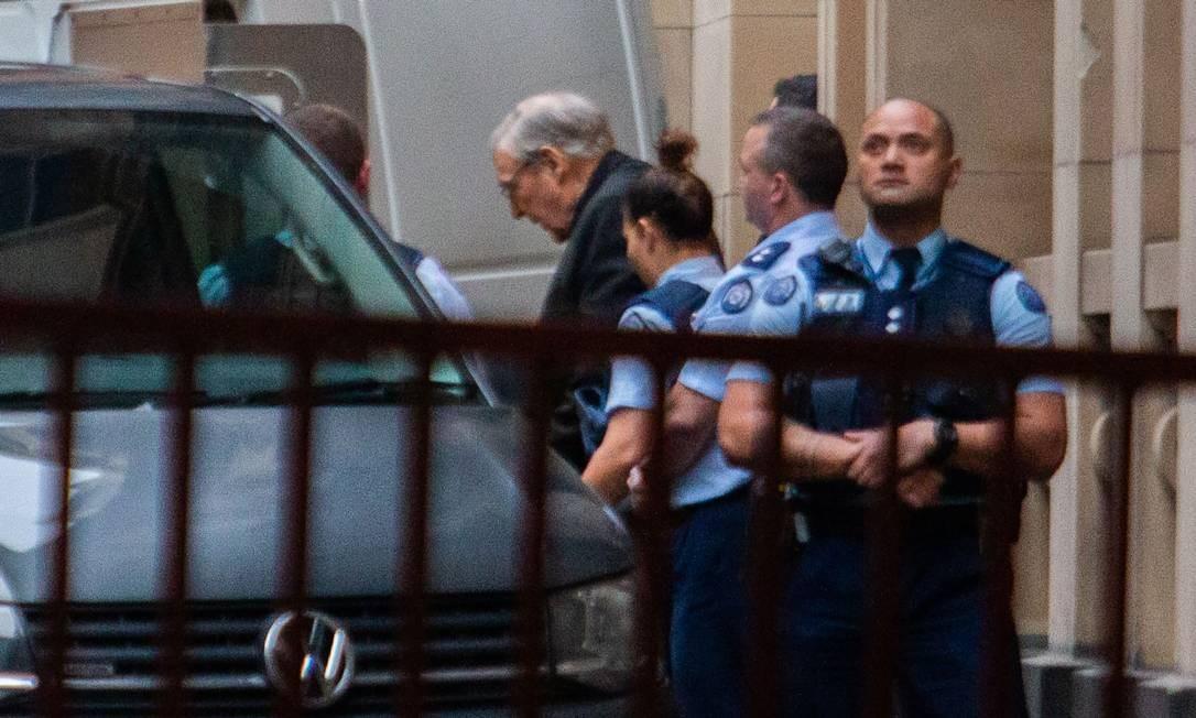 Cardeal George Pell é escoltado após deixar a Suprema Corte do estado de Victoria Foto: ASANKA BRENDON RATNAYAKE / AFP