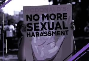 Uma funcionária do McDonald's segura, em setembro de 2018, um cartaz pedindo pelo fim do assédio sexual no ambiente de trabalho, em Chicago. Recentemente, foram divulgados dezenas de novos casos de assédio na gigante do fast-food Foto: Arte de Nina Millen sobre foto de Jushua Lott/AFP/18-09-2018