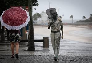 Pedestre se protege da chuva na Praia do Arpoador Foto: Pablo Jacob