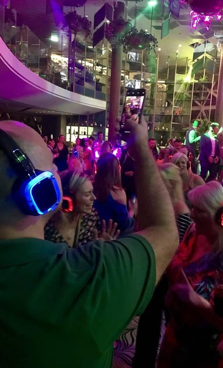 Passageiros do Celebrity Edge dançam na Silent Disco, onde a música ambiente foi substituída pela tocada em headphones individuais Foto: Luã Marinatto / Agência O Globo