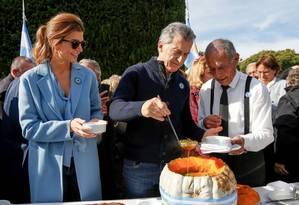 Mauricio Macri com a mulher, Juliana Awada, servindo refeição na residência oficial de Los Olivos Foto: AFP