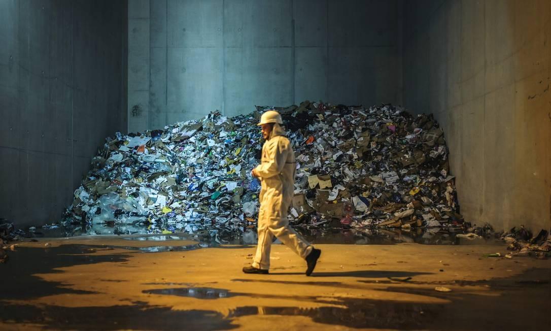 Um funcionário do centro de triagem Syctom passa por uma pilha de lixo no dia de sua inauguração, no 17º distrito de Paris, França. Foto: LUCAS BARIOULET / AFP