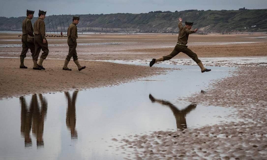 Um homem pula sobre uma poça de chuva enquanto caminha pela praia de Omaha com dois colegas entusiastas da Segunda Guerra Mundial vestindo um uniforme dos EUA em Saint-Laurent-sur-Mer, Normandia. Foto: JOEL SAGET / AFP
