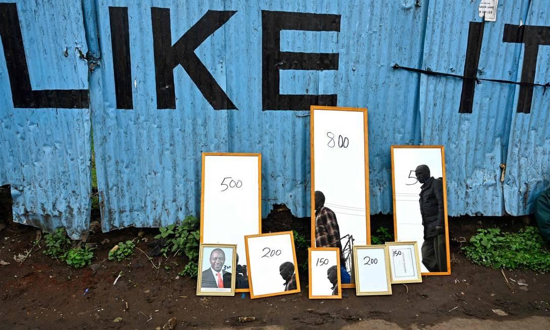 Homens passam por um retrato do presidente queniano, Uhuru Kenyatta, exibido ao lado de espelhos à venda no distrito de Makadara, em Nairóbi. Foto: SIMON MAINA / AFP
