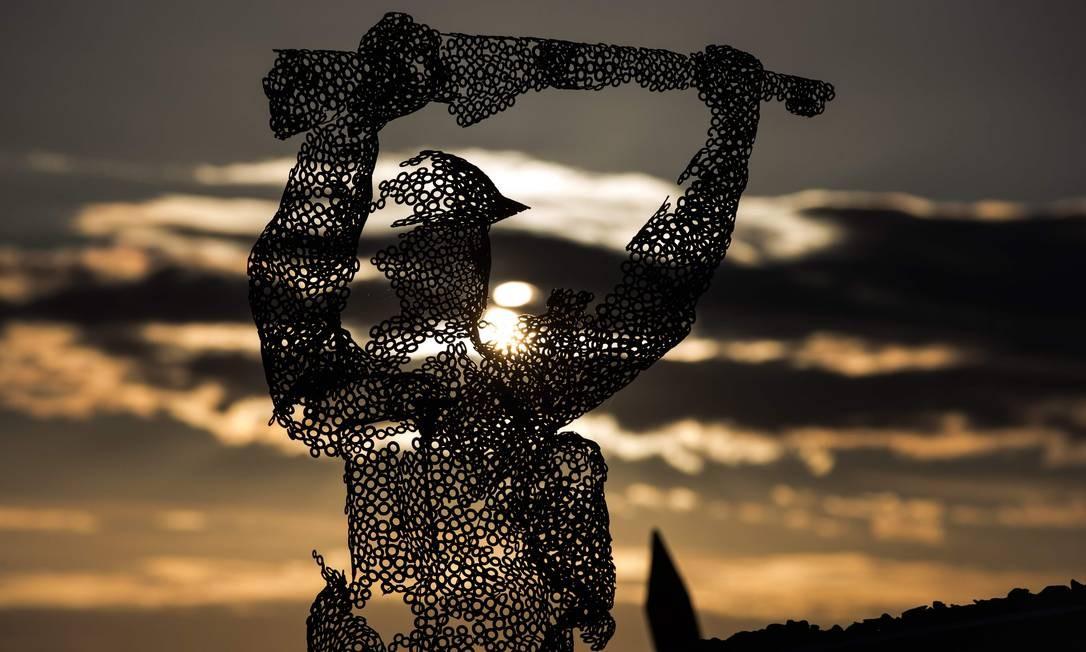 o sol brilhando através de uma escultura de soldado britânico em Arromanches, na Normandia, durante as comemorações do Dia D. Foto: JOEL SAGET / AFP