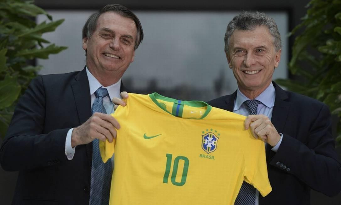 Os presidentes Jair Bolsonaro e Mauricio Macri posam com uma camisa da seleção brasileira durante almoço oficial na Casa Rosada, em Buenos Aires - 06/05/2019 Foto: JUAN MABROMATA / AFP