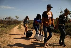 Migrantes venezuelanos caminham por uma trilha em direção à fonteira com Brasil, na cidade fronteiriça de Pacaraima Foto: Pilar Olivares / REUTERS