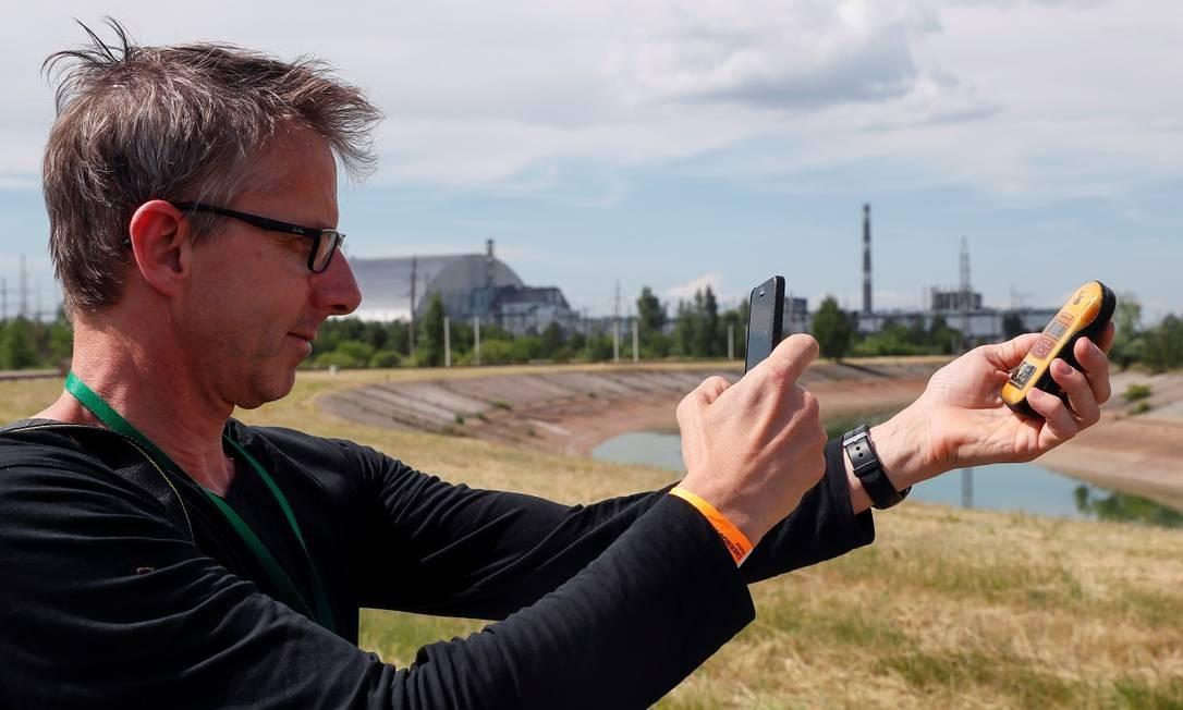 """Turista fotografa um dosímetro para medir radiação perto do Novo Confinamento Seguro, estrutura montada para aumentar a segurança do """"Sarcófago"""" de Chernobyl Foto: VALENTYN OGIRENKO / REUTERS"""