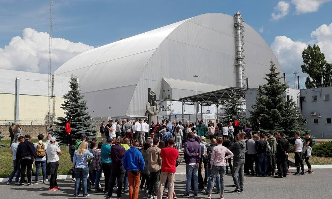 """Grupos de turistas se reúnem do lado de fora do Novo Confinamento Seguro, estrutura que foi instalada em 2017 para reforçar o """"Sarcófago"""" de Chernobyl Foto: VALENTYN OGIRENKO / REUTERS"""