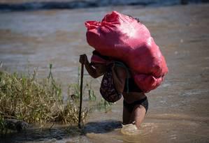 Um homem atravessa ilegalmente o rio Suchiate levando produtos de El Carmen, na Guatemala, para Talisman, no estado de Chiapas, México Foto: PEDRO PARDO / AFP