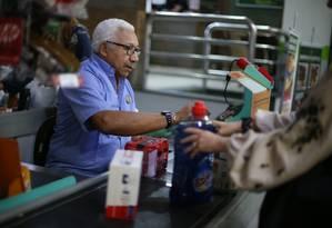 Oportunidade. Romeu da Conceição opera caixa num supermercado em Botafogo, no Rio, há 11 anos: casos como o dele são raros. No comércio, menos de 10% dos empregados têm mais de 50 anos Foto: Pedro Teixeira / Agência O Globo