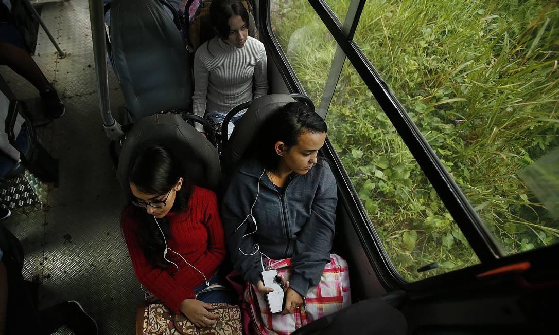 As alunas Julia Abreu Cabral (à esquerda) e Natália da Conceição Fraga para estudar usam o transporte escolar, em Cachoeiras de Macacu. Os estudantes contam que, às vezes, o ônibus não passa, porque não tem óleo ou quebra no caminho. Nos dias de chuva, com a estrada barrenta, o transporte não aparece Foto: Antonio Scorza / Agência O Globo