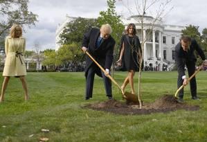 Donald Trump e Emmanuel Macron, acompanhados de suas esposas, plantam uma muda nos jardins da Casa Branca Foto: JIM WATSON / AFP/ 23-04-2018