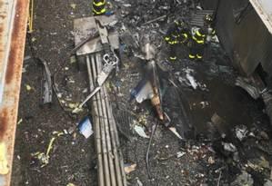 Bombeiros trabalham no local da queda de um helicóptero no topo de um prédio em Manhattan Foto: HO / AFP