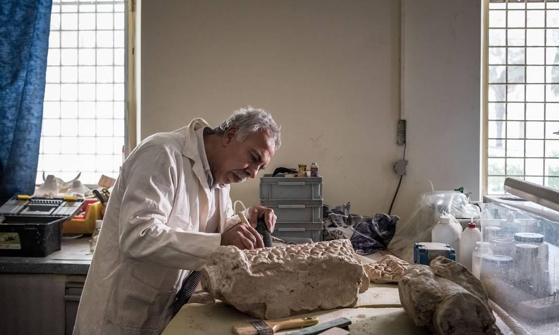 Cientista trabalha para restaurar peça de coluna decorativa de 1500 anos no Museu do Iraque, em Bagdá; saqueado em 2003, instituição tem majestosa coleção de arte milenar Foto: SERGEY PONOMAREV / NYT