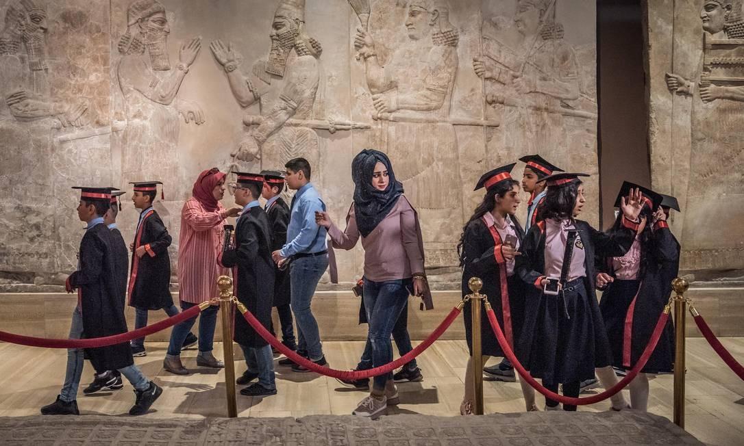 Visitantes passam por murais assirios no Museu do Iraque; local foi reaberto em 2015, após ter sido saqueado em 2003, a partir de restaurações com ajuda de países europes Foto: SERGEY PONOMAREV / NYT