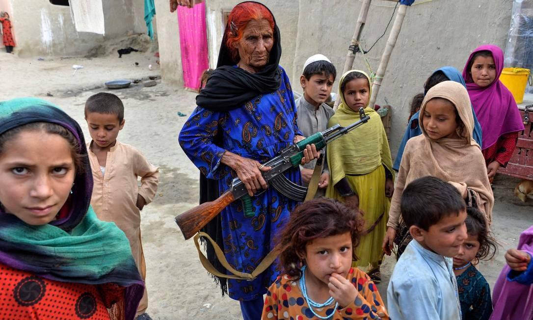 Mulher afegã leva fuzil para proteger crianças no caminho até a escola. O Afeganistão foi apontado como o país menos pacífico do mundo pelo estudo do Instituto para Economia e Paz. Quase 18 anos depois do início da guerra, o país vive um aumento na violência, no terrorismo e na instabilidade política Foto: NOORULLAH SHIRZADA / AFP