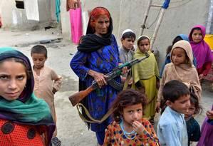 Mulher afegã leva fuzil para proteger crianças no caminho até a escola. O Afeganistão foi apontado como o país menos pacífico do mundo pelo estudo do Instituto para Economia e Paz. Quase 18 anos depois do início da guerra, o país vive um aumento na violência, no terrorismo e na instabilidade política. Foto: NOORULLAH SHIRZADA / AFP