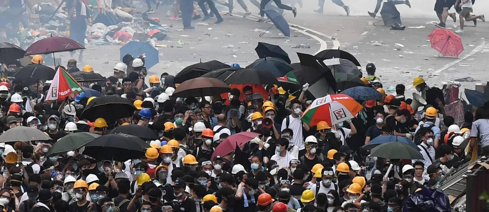 Manifestantes correm após a polícia usar gás de efeito lacrimogênio Foto: ANTHONY WALLACE / AFP