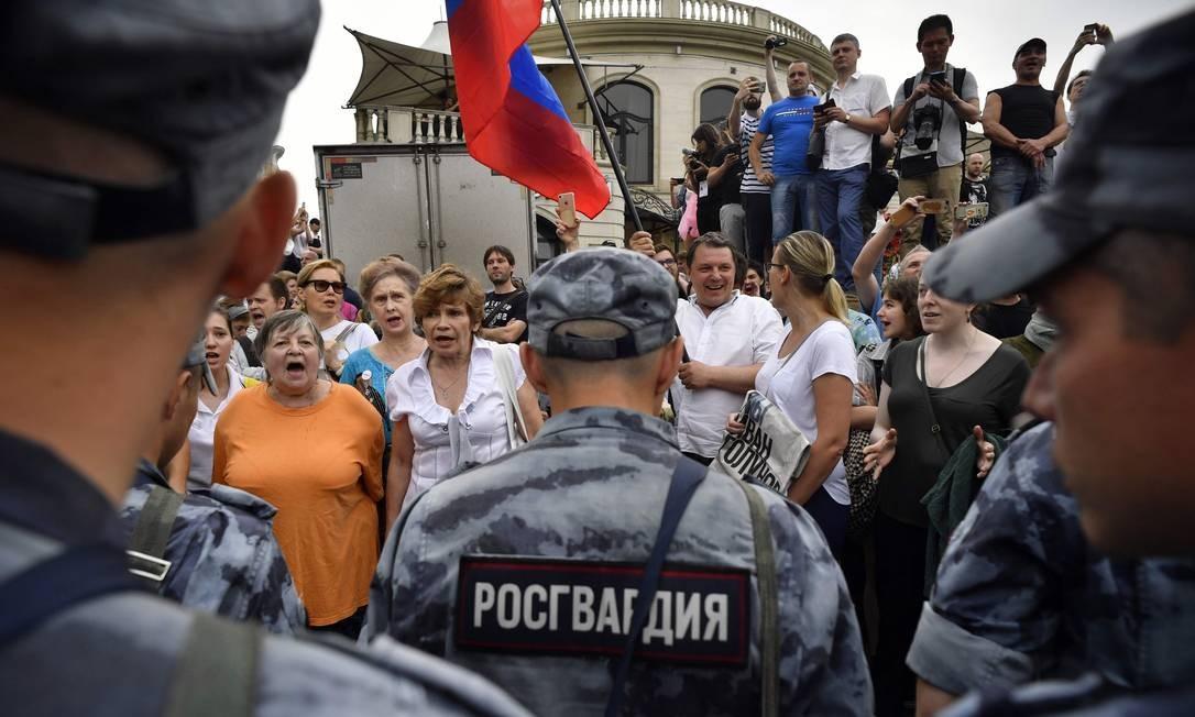 Policiais russos impedem passagem de manifestantes durante protesto contra a impunidade policial, em Moscou. Mais de 100 pessoas foram presas Foto: Alexander Nemenov / AFP